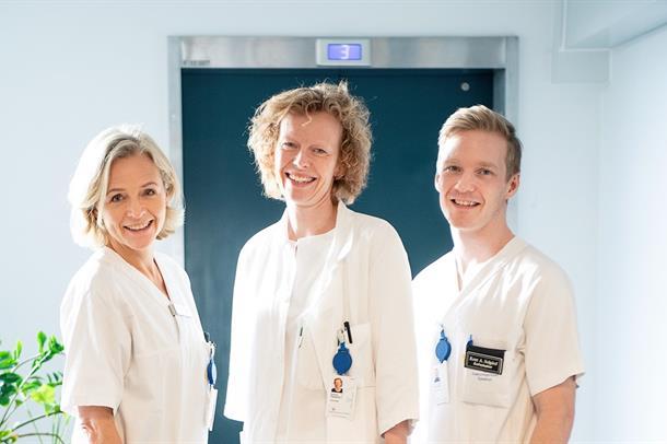 Tre ansatte i hvitt poserer i avdelingen