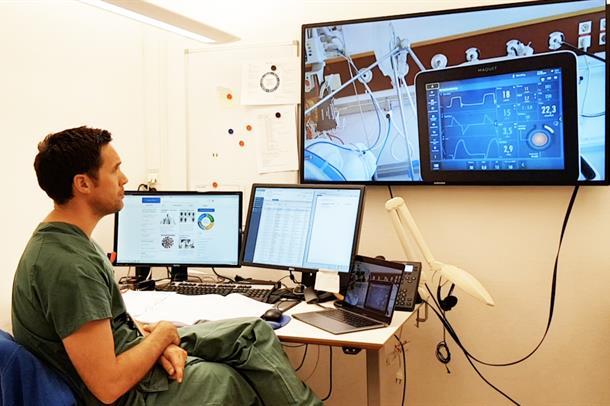 Lege på vaktrom mens han følger med på storskjerm på hva som skjer på pasientrommet