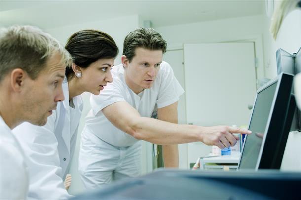 TRe hvitkledde ansatte ser og peker på en dataskjerm