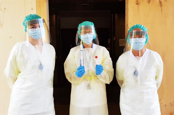 Tre sykepleiere i fullt smittevernutdtyr og med testutstyr foran inngangen til teststasjonen