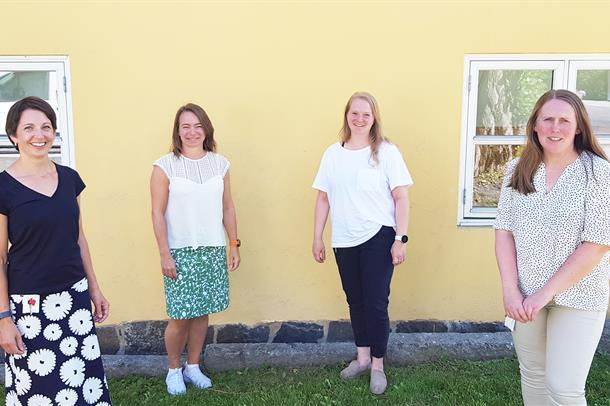 De fire involverte fra revma og IKT  poserer langs en husvegg ute i solen