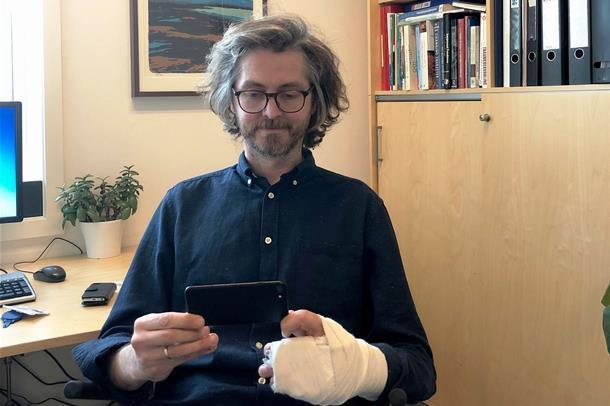 Psykolog Espen Eugen Gustavsen sitter i stol og holder et nettbrett