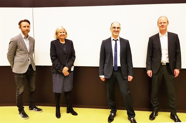 Kiaras, hovedveilederen og de to biveilederne står langs med en vegg og smiler