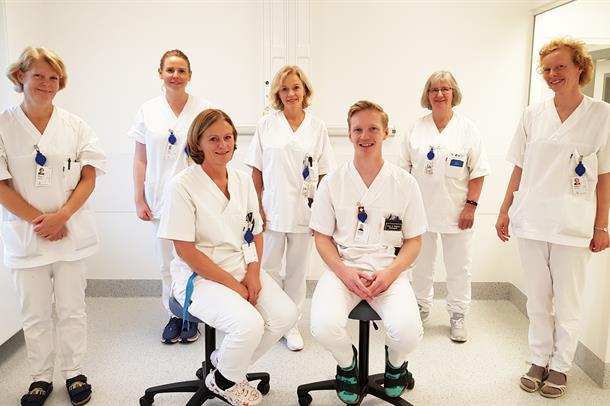 syv hvitkledde sykepleiere og leger på gruppebilde